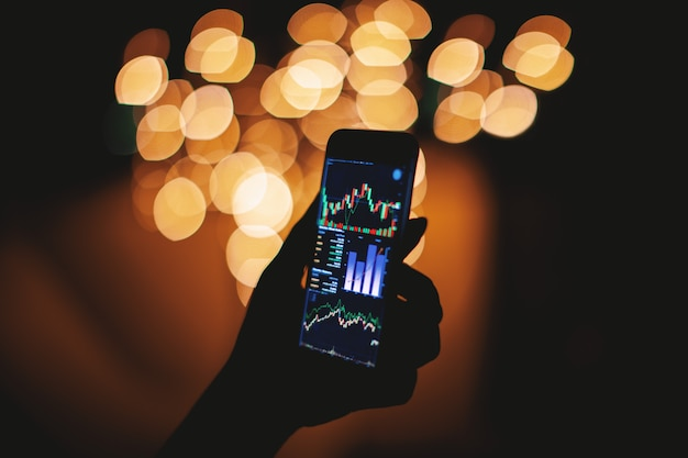 Mão de silhueta segurando o telefone inteligente com exibição de negociação de ações com luz de fundo