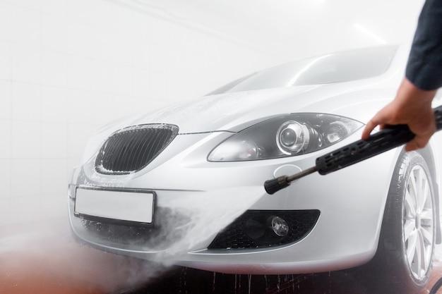 Mão de técnico com mangueira no serviço de lavagem de carros
