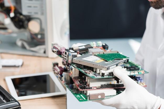 Mão de técnico masculino usando luvas segurando as peças do computador