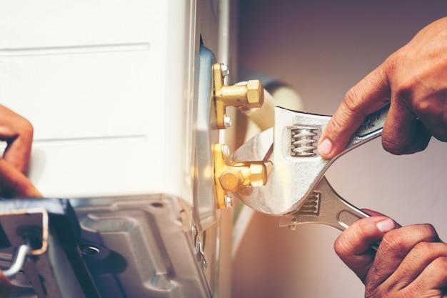 Mão de técnico usando chave de reparo para apertar a unidade exterior de ar condicionado