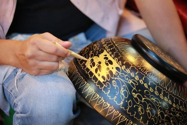 Mão de tinta cor ouro na tigela, tailândia