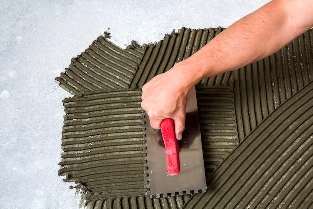 Mão de trabalhador com ferramenta de espátula para instalação de azulejos, tornando o adesivo de argamassa no chão