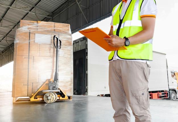 Mão de trabalhador de armazém segurando a área de transferência, inspecionando detalhes de carga de carga em um caminhão