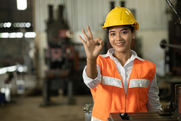 Mão de trabalhador de mulheres asiáticas mostrando ok ou bom trabalho, sem problemas, sinal na fábrica de trabalho