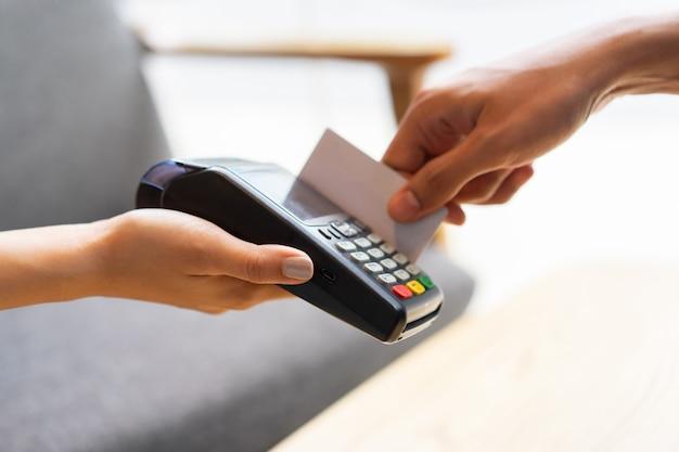 Mão de trabalhador garçonete dando uma máquina de dinheiro bancário eletrônico para receber a compra do cliente