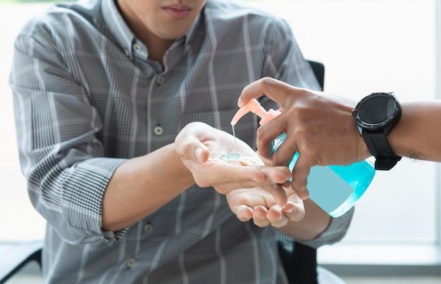 Mão de trabalhador homem asiático desinfetante álcool gel esfregar mãos limpas higiene proteger