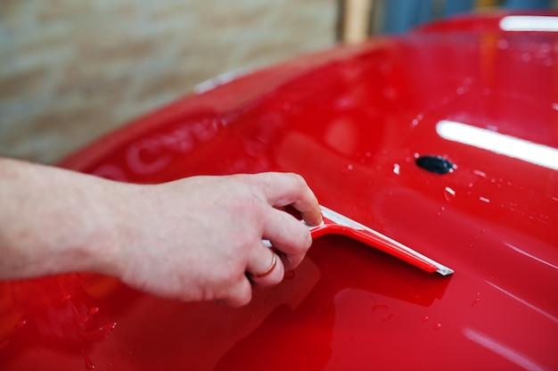 Mão de trabalhador lavando carro vermelho na garagem de detalhes