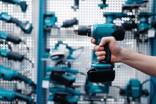 Mão de trabalhador masculino segurando furadeira elétrica em loja de ferramentas
