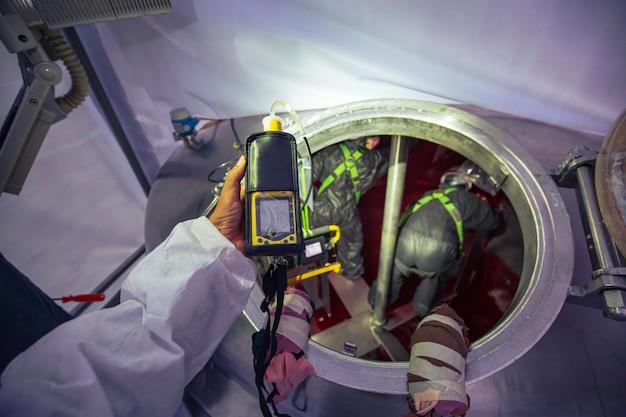 Mão de trabalhador segurando detector de gás, inspeção e teste de segurança de gás no tanque de aço inoxidável frontal para trabalhar dentro de confinamento