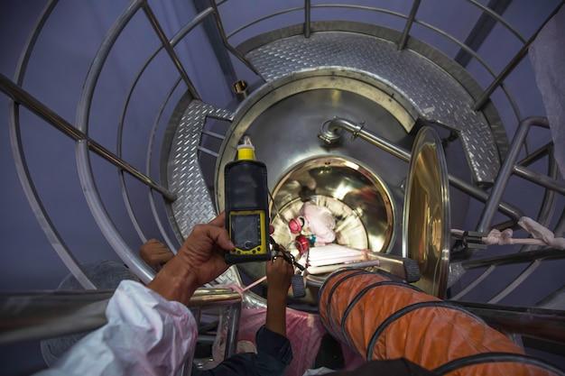 Mão de trabalhador segurando detector de gás, inspeção, segurança, teste de gás no bueiro frontal, tanque brilhante inoxidável, trabalhador masculino dentro de espaço confinado