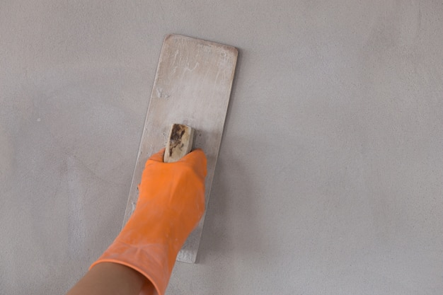 Mão de trabalhador usar espátula reboco de concreto na parede