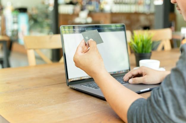 Mão de trabalho em linha do homem de negócios que guarda o cartão de crédito e que usa o portátil no café.