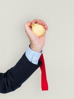 Mão de trajes de negócios segurando a medalha