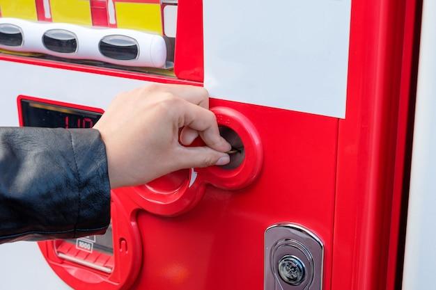 Mão de turista inserir moedas na máquina de venda automática