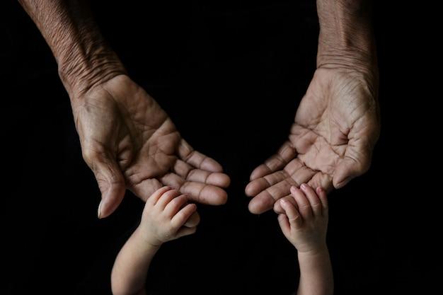 Mão de um bebê jovem tocando a mão antiga dos idosos (foco suave e embaçado)