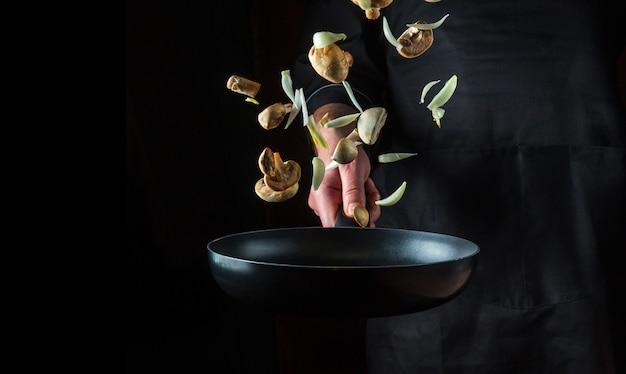 Mão de um chef profissional joga pedaços de cebola e cogumelos na frigideira em um fundo preto