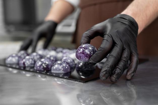 Mão de um chefão confeiteiro colocando chocolates coloridos em uma superfície de espelho preta