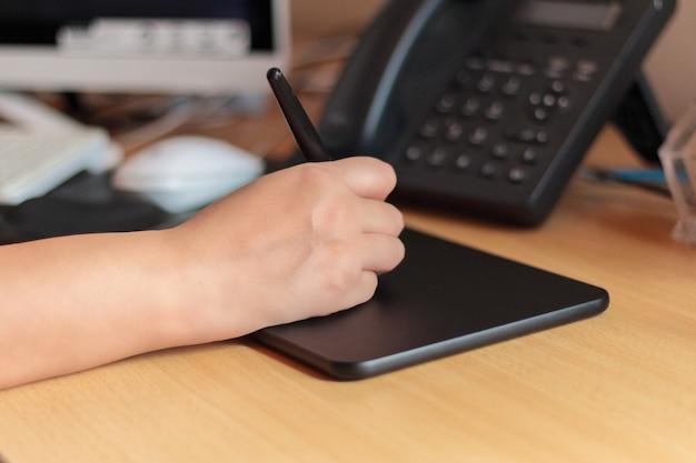 Mão de um desenhista com uma mesa digitalizadora com o computador