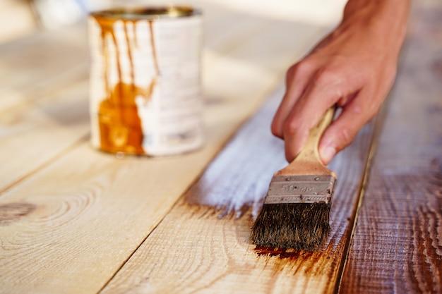 Mão de um designer carpinteiro lubrificando uma mesa autônoma autêntica com uma escova grande em um ambiente de oficina.