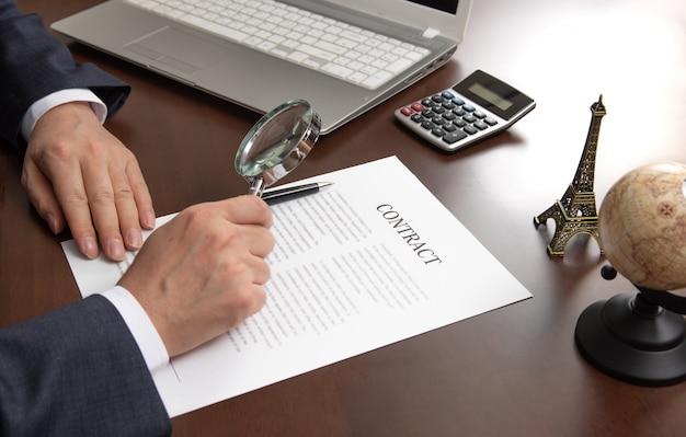 Mão de um empresário, olhando para um documento de contrato através de uma lupa.