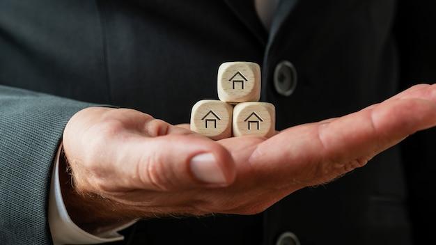 Mão de um empresário ou corretor de imóveis segurando três dados de madeira com formas de casa neles.