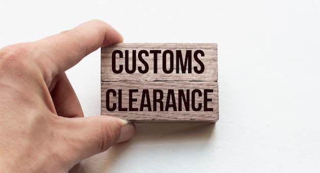 Mão de um empresário segurando blocos de madeira imagem conceitual texto customs clearance