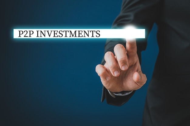 Mão de um empresário tocando uma barra de pesquisa brilhante com sinais de investimentos p2p na interface virtual.