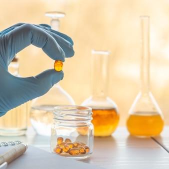 Mão de um farmacêutico segura uma cápsula com vitaminas sobre potes de ingredientes no laboratório