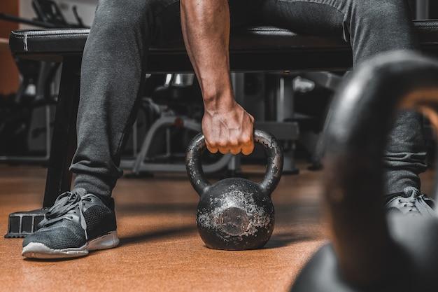 Mão de um fim muscular considerável novo do instrutor da aptidão acima com um peso.