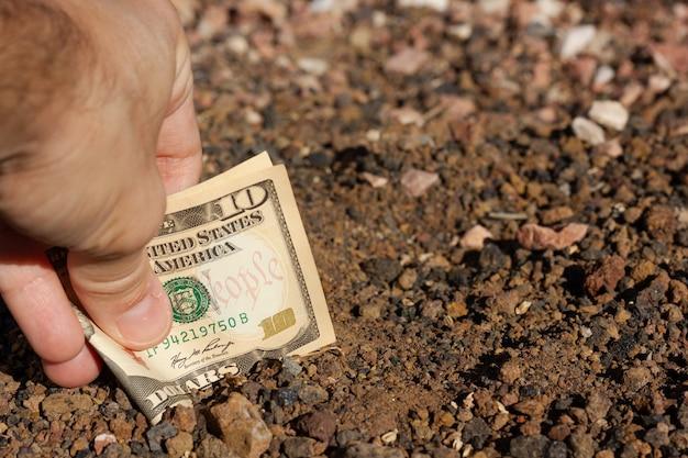 Mão de um homem colocando uma nota de dez dólares dobrada no solo chão propriedade dinheiro investidor terra investimento