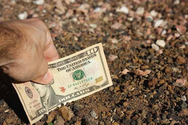 Mão de um homem colocando uma nota de dez dólares no solo, terreno, conceitos de projeto de barganha de investimento de terras