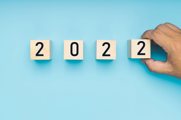 Mão de um homem colocou um bloco de madeira do ano novo de 2022 em um fundo azul suave