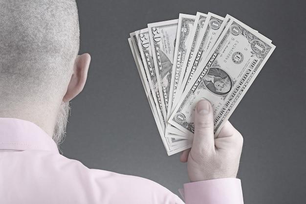 Mão de um homem com uma camisa segurando notas de dólar. finanças e estabilidade. riqueza e crédito. dinheiro e auto-indexação