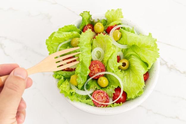 Mão de um homem comendo uma salada fresca e saudável em uma tigela. comida mediterrânea