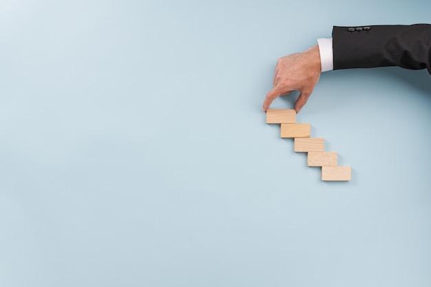 Mão de um homem de negócios fazendo escada de estacas de madeira