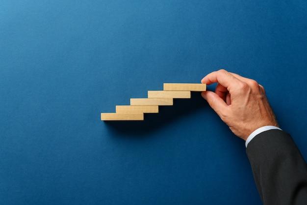 Mão de um homem de negócios fazendo uma escada como estrutura de estacas de madeira em azul