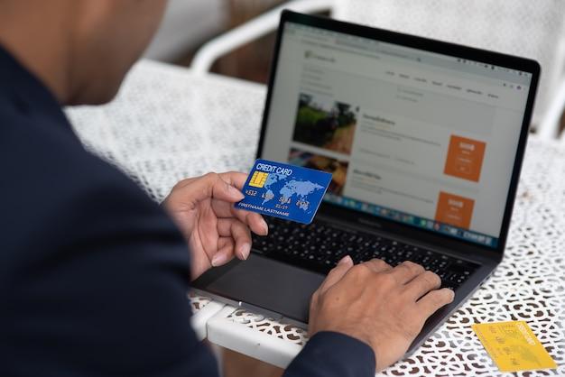 Mão de um homem de negócios que prende uma informação do cartão e da impressão de crédito em um computador.