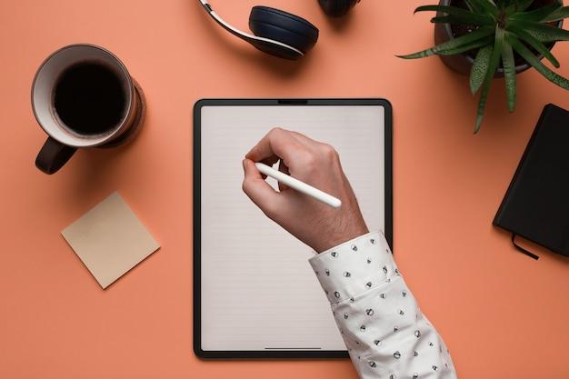 Mão de um homem, escrevendo notas em um tablet digital de maquete