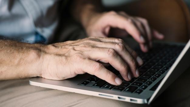 Mão de um homem idoso digitando no laptop