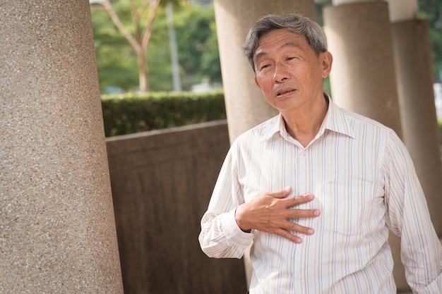 Mão de um homem idoso segurando refluxo ácido