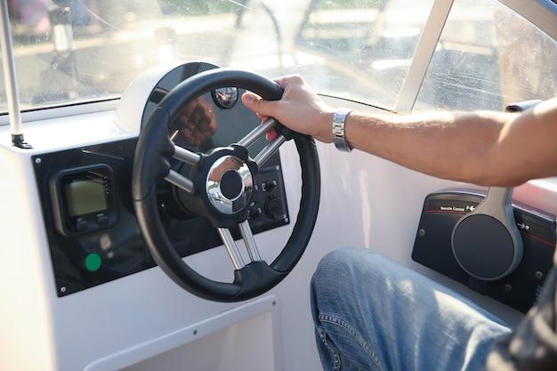 Mão de um homem no volante de um barco a motor