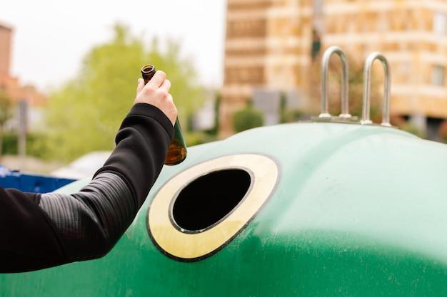 Mão de um homem reciclando uma garrafa de vidro em um recipiente. conceito de reciclagem e cuidado com o meio ambiente