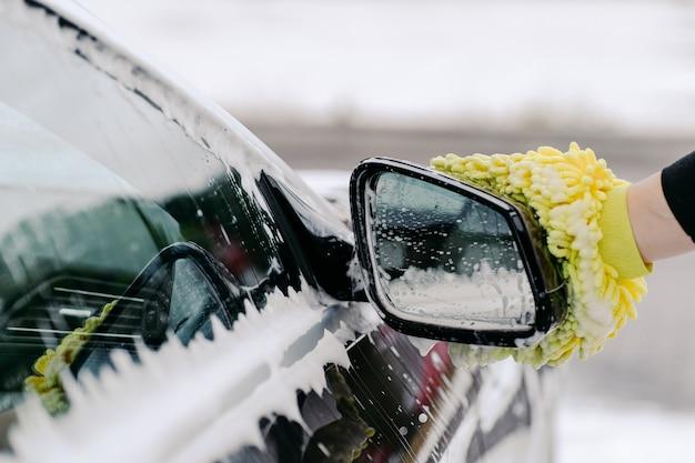 Mão de um homem segurando a janela lateral do carro de lavagem de esponja amarela com espuma no serviço de limpeza. limpeza do automóvel. limpeza detalhada do veículo