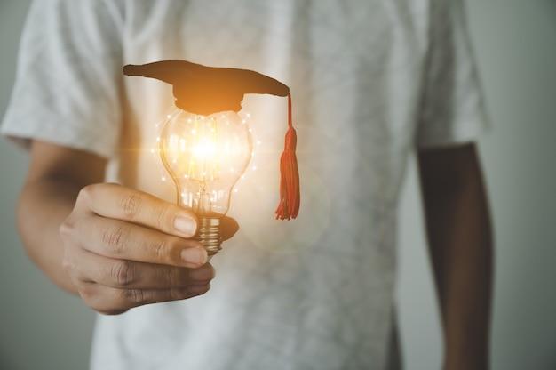 Mão de um homem segurando a lâmpada. conceito de educação e pensamento de ideias criativas e inovação tecnológica futura