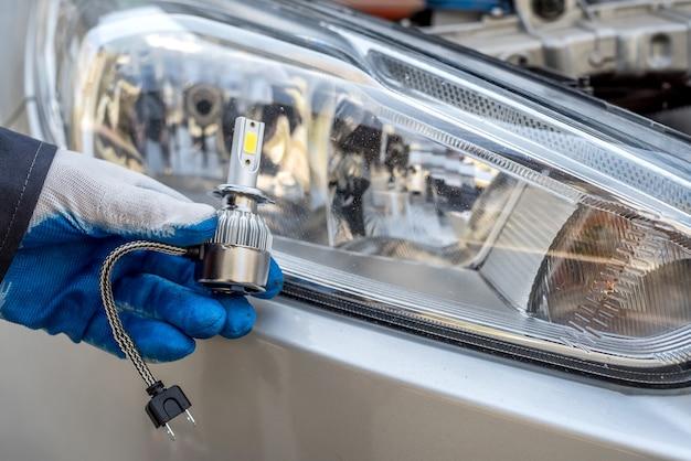 Mão de um homem segurando a lâmpada do farol do carro para conserto de automóveis, close-up