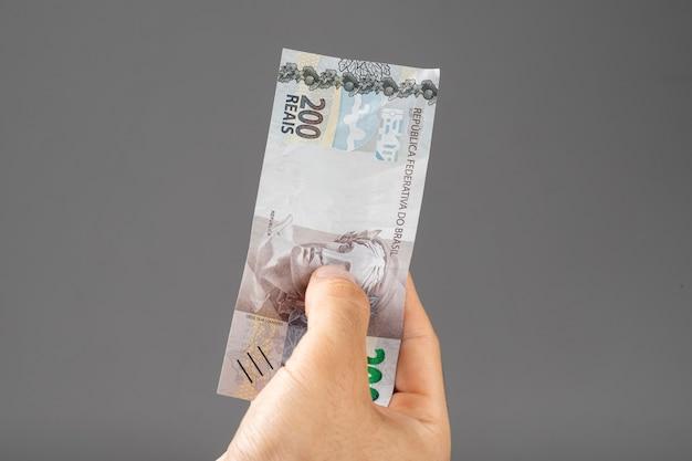Mão de um homem segurando notas brasileiras