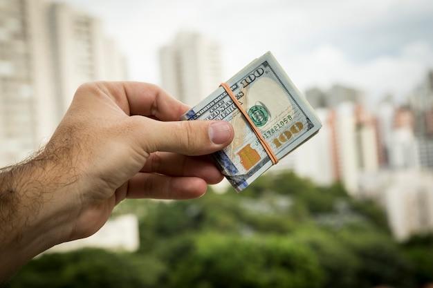 Mão de um homem segurando notas de dólar em frente a uma paisagem da cidade