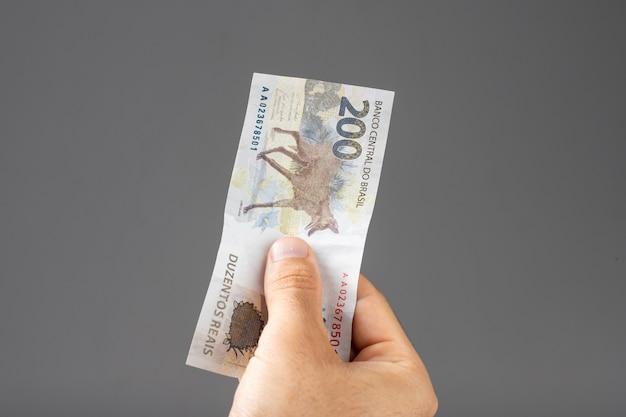 Mão de um homem segurando notas de reais