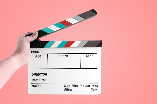 Mão de um homem segurando uma lousa de filme de cinema isolada