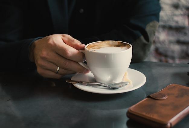 Mão de um homem segurando uma xícara de café de cappuccino em uma mesa no refeitório.